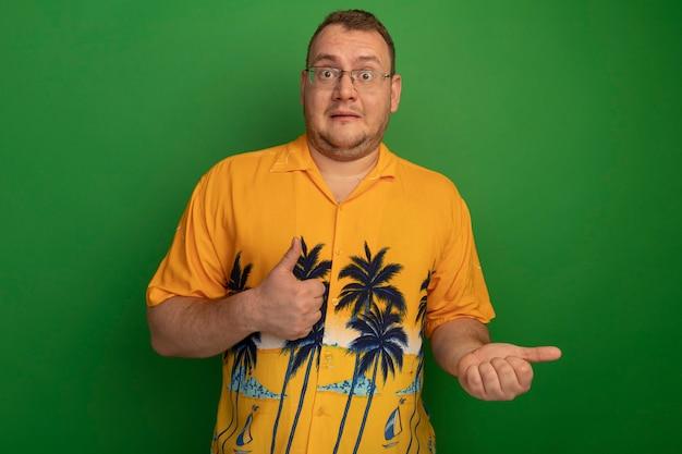 Mężczyzna w okularach i hawajskiej koszuli zdezorientowany pokazując kciuki do góry stojąc nad zieloną ścianą