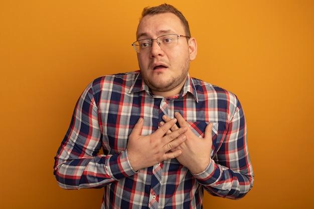 Mężczyzna w okularach i koszuli w kratę patrzy na bok, z rękami na piersi, zmartwiony, stojąc nad pomarańczową ścianą