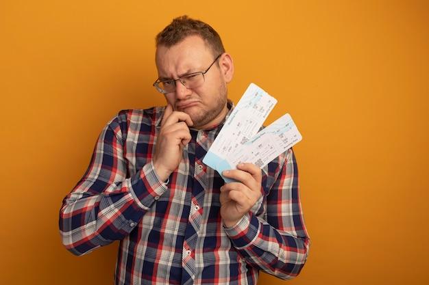 Mężczyzna w okularach i koszuli w kratkę, trzymając bilety lotnicze, patrząc na bok z ręką na brodzie, marszcząc brwi, niezadowolony, stojąc nad pomarańczową ścianą