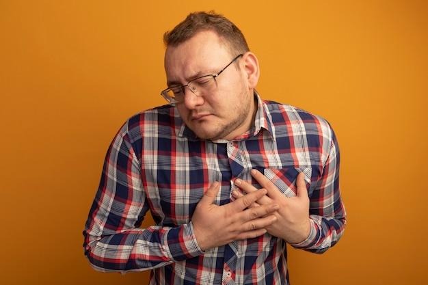 Mężczyzna w okularach i koszuli w kratkę, trzymając się za ręce na piersi, czuje wdzięczność stojąc nad pomarańczową ścianą