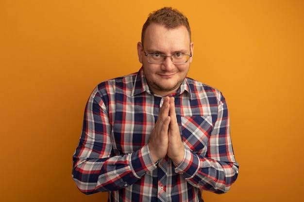 Mężczyzna w okularach i koszuli w kratkę, trzymając się za ręce razem, czekając na coś stojącego nad pomarańczową ścianą