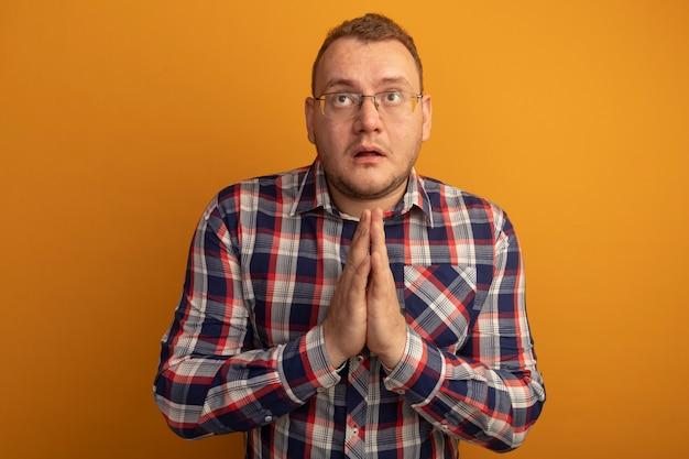 Mężczyzna w okularach i koszuli w kratkę, trzymając się za ręce razem, jak modląc się, patrząc w górę z nadzieją stojącą nad pomarańczową ścianą
