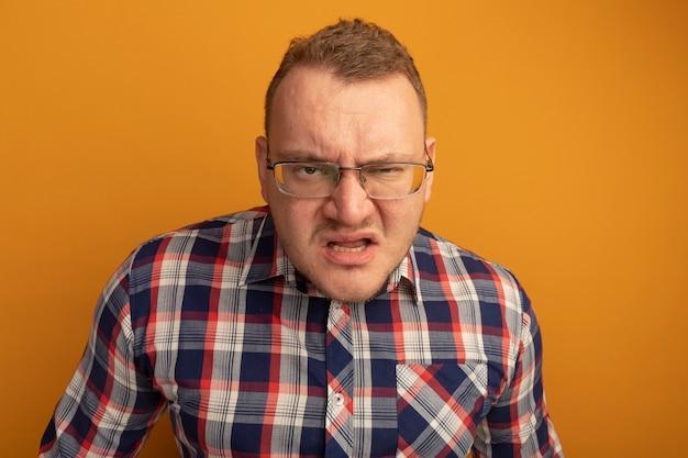 Mężczyzna w okularach i koszuli w kratkę z gniewną twarzą stojącą nad pomarańczową ścianą