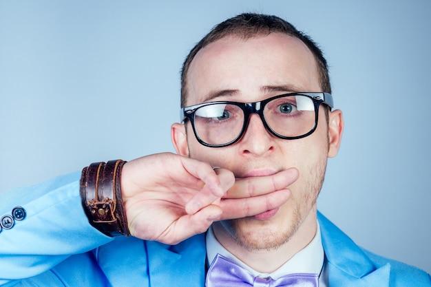 Mężczyzna w okularach i niebieskim eleganckim garniturze zakrywa usta dłonią. pojęcie tajemnicy, poufności i prywatności