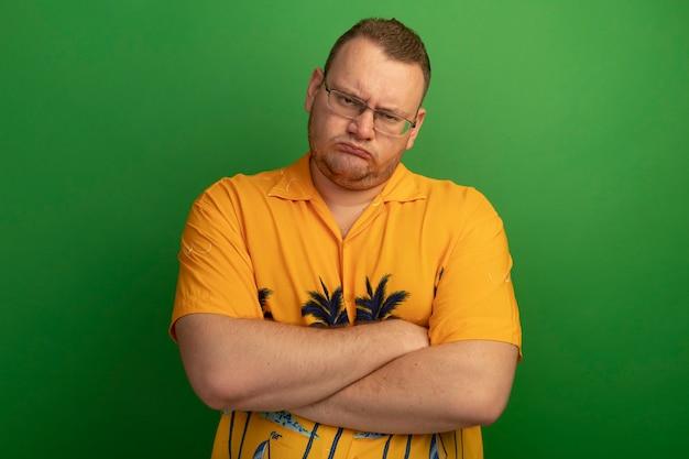 Mężczyzna w okularach i pomarańczowej koszuli z zachmurzoną twarzą z założonymi rękami, stojący nad zieloną ścianą