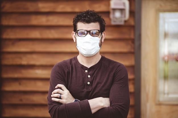 Mężczyzna w okularach i sanitarnej masce na twarz ze skrzyżowanymi rękami przed drewnianą ścianą