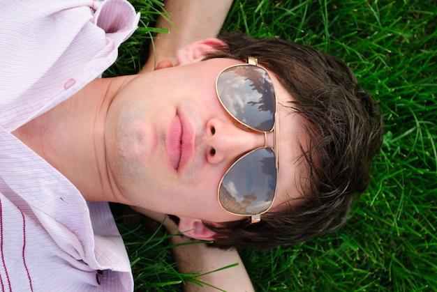 Mężczyzna w okularach leży na trawie i patrzy w niebo. portret na zewnątrz
