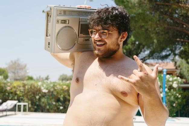 Mężczyzna w okularach na sobie kasetę radiową na ramieniu