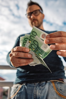 Mężczyzna w okularach na sobie niebieską koszulę. i trzymając stos pieniędzy.