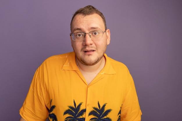 Mężczyzna w okularach na sobie pomarańczową koszulę szczęśliwy i pozytywny uśmiechnięty stojący nad fioletową ścianą