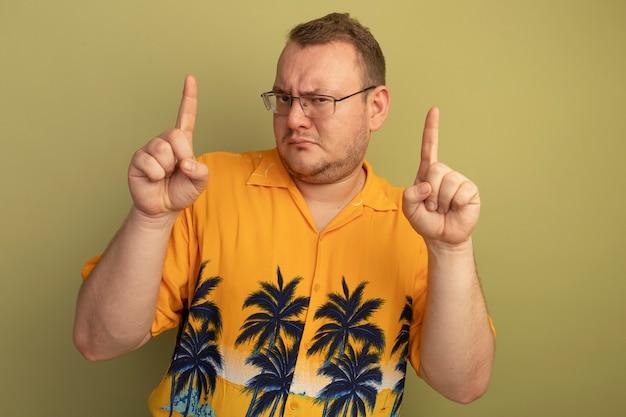 Mężczyzna w okularach na sobie pomarańczową koszulę z poważną twarzą pokazującą palniki wskazujące stojących nad zieloną ścianą