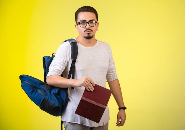 Mężczyzna w okularach optique trzyma książkę.