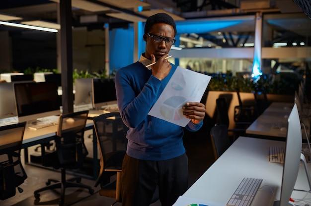 Mężczyzna w okularach patrzy na wykresy, biurowy styl życia