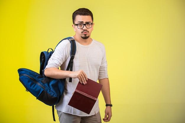 Mężczyzna w okularach, plecaku i książce.