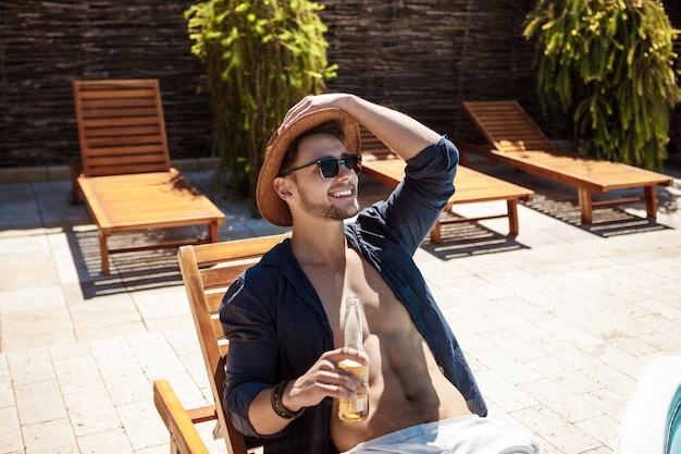 Mężczyzna w okularach przeciwsłonecznych i kapeluszu pije piwo, siedzi na bryczce