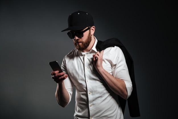 Mężczyzna w okularach przeciwsłonecznych i koszulowym mieniu telefon i patrzeć daleko od