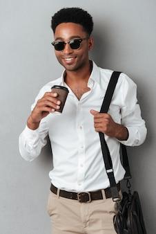 Mężczyzna w okularach przeciwsłonecznych jest ubranym torbę i trzyma filiżankę kawy