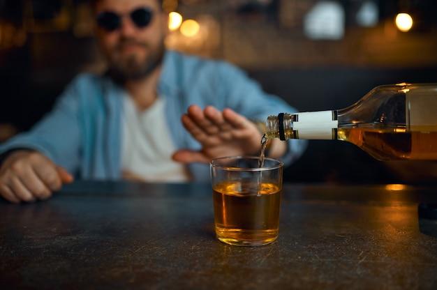 Mężczyzna w okularach przeciwsłonecznych odmawia picia alkoholu przy kasie w barze. jeden mężczyzna odpoczywający w pubie, ludzkie emocje, zajęcia rekreacyjne, życie nocne