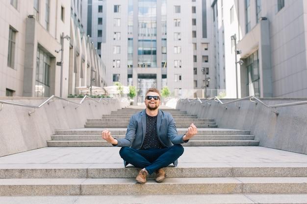 Mężczyzna w okularach przeciwsłonecznych siedzi na betonowych schodach w pozie medytacji