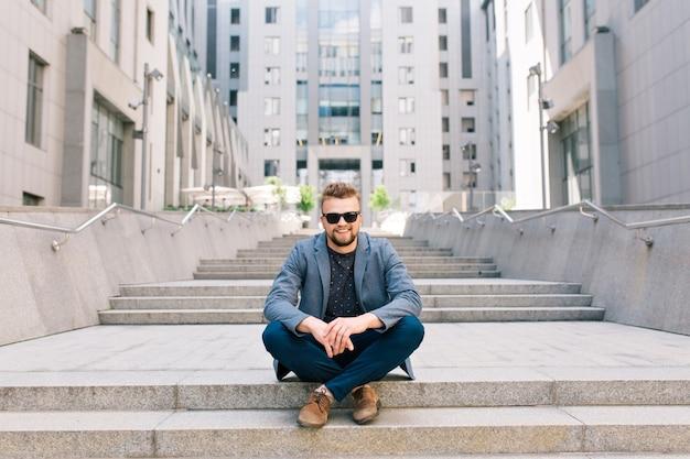 Mężczyzna w okularach przeciwsłonecznych siedzi na betonowych schodach