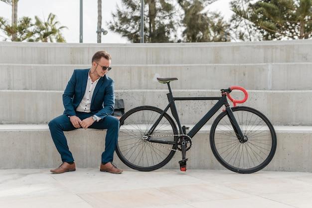 Mężczyzna w okularach przeciwsłonecznych siedzi obok roweru na zewnątrz