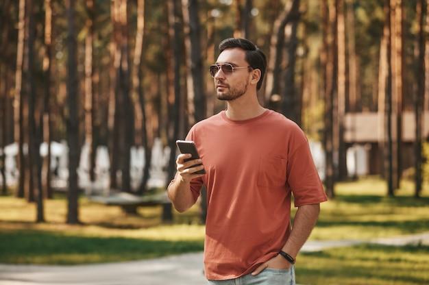 Mężczyzna w okularach przeciwsłonecznych ze smartfonem w dłoni