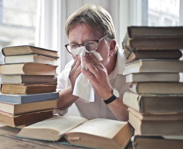 Mężczyzna w okularach przy książkach wydmuchuje nos