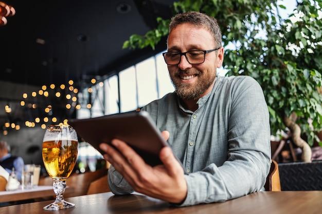 Mężczyzna w okularach siedzi w barze po pracy i używa tabletu do zawieszenia w mediach społecznościowych.