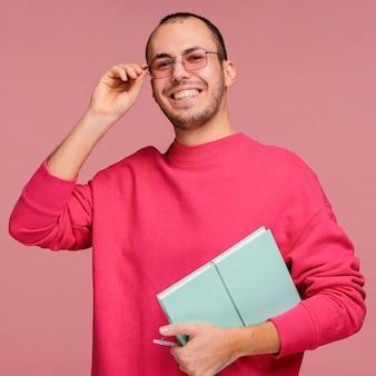 Mężczyzna w okularach trzyma książkę i się śmieje