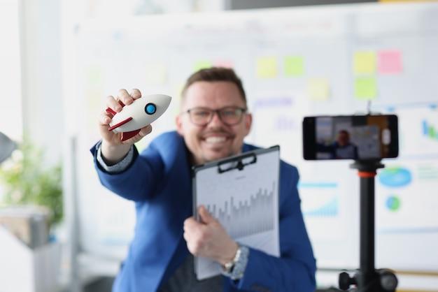 Mężczyzna w okularach trzymający rakietę-zabawkę i dokumenty z wykresami przed kamerą telefonu komórkowego