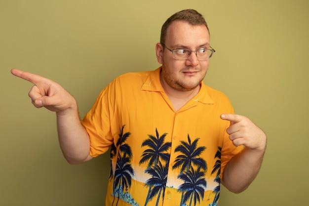 Mężczyzna w okularach, ubrany w pomarańczową koszulę, patrząc na bok ze sceptycznym wyrazem twarzy, wskazując palcami wskazującymi na stronę stojącą nad zieloną ścianą