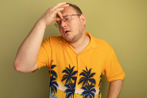 Mężczyzna w okularach w pomarańczowej koszuli dotykający nosa między zamkniętymi oczami, zmęczony i znudzony, stoi nad zieloną ścianą