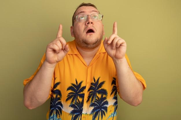 Mężczyzna w okularach w pomarańczowej koszuli patrząc w górę zaskoczony i zmartwiony wskazując palcami wskazującymi w górę, stojąc nad zieloną ścianą