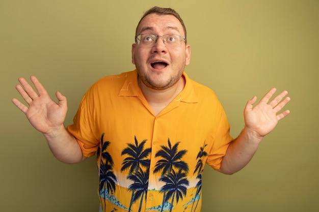 Mężczyzna w okularach w pomarańczowej koszuli patrząc w górę zaskoczony podnosząc dłonie szczęśliwy i wesoły stojący nad jasną ścianą