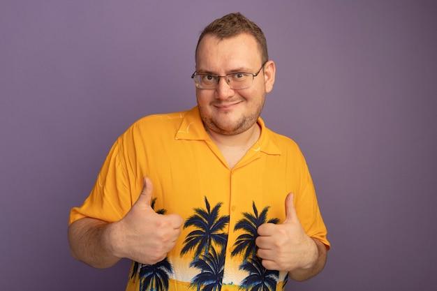 Mężczyzna w okularach w pomarańczowej koszuli szczęśliwy i pozytywny pokazując kciuki do góry stojąc nad fioletową ścianą