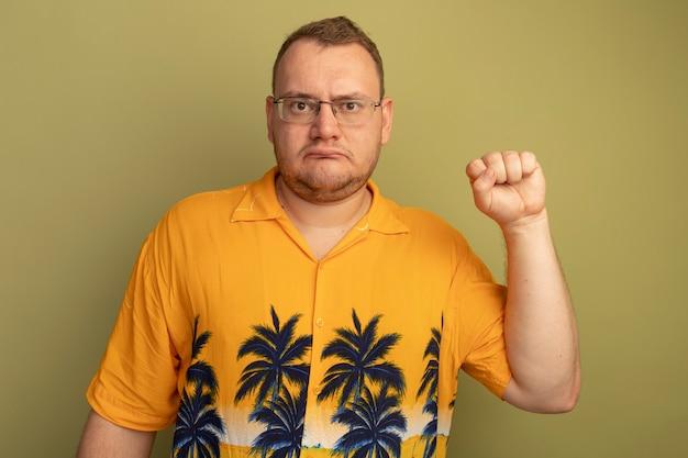Mężczyzna w okularach w pomarańczowej koszuli z poważną twarzą unoszącą pięść jak zwycięzca stojący nad zieloną ścianą