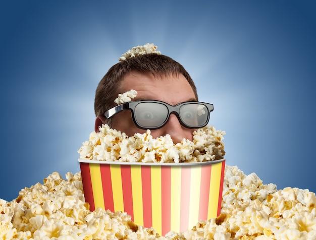 Mężczyzna w okularach w wiadrze popcornu na niebiesko