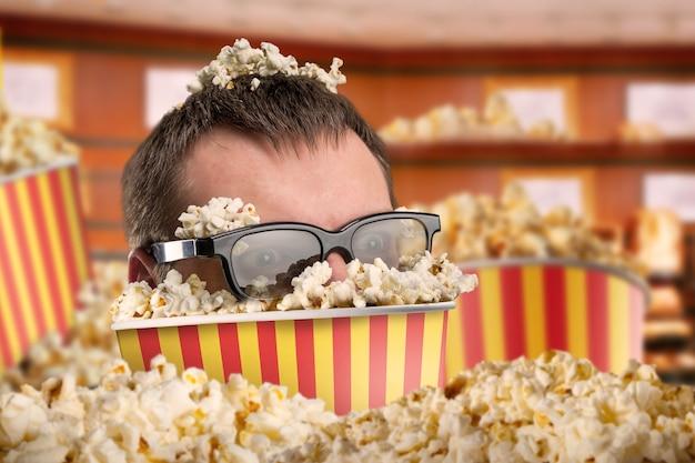 Mężczyzna w okularach w wiadrze popcornu