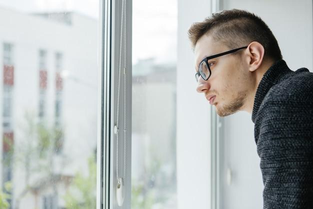 Mężczyzna w okularach wygląda przez okno