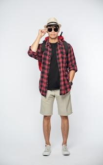 Mężczyzna w okularach wyrusza w podróż, nosi kapelusz i nosi plecak