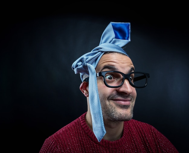 Mężczyzna w okularach z krawatem na głowie.