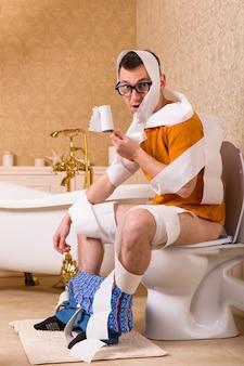 Mężczyzna w okularach zawinięty w papier toaletowy siedzi na misce. wnętrze łazienki w stylu vintage