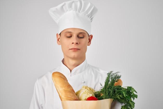 Mężczyzna w opakowaniu odzieży szefa kuchni z artykułami spożywczymi, gotowanie żywności w kuchni