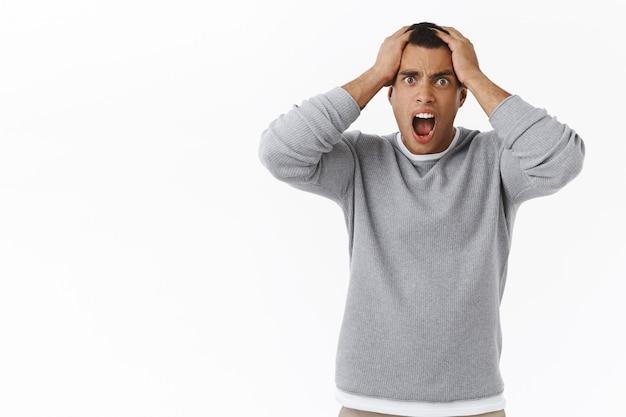 Mężczyzna w panice chwyta się za głowę i krzyczy pod presją