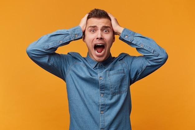 Mężczyzna w panice złapał się za głowę, głośno krzycząc, doszło do niepowodzenia klęski, w dżinsowej koszuli