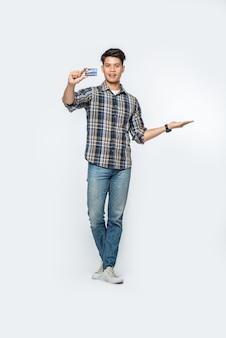 Mężczyzna w pasiastej koszuli otwiera lewą rękę i trzyma kartę kredytową