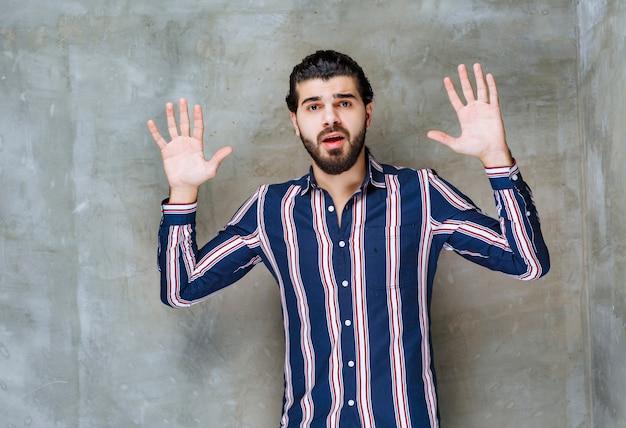 Mężczyzna w pasiastej koszuli otwierając rękę i odmawiając.