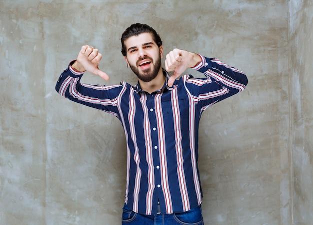 Mężczyzna w pasiastej koszuli pokazując kciuk w dół.