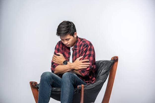 Mężczyzna w pasiastej koszuli siedzi chory, siedzi na krześle i krzyżuje ramiona.