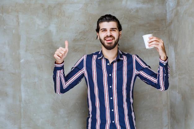 Mężczyzna w pasiastej koszuli trzymający białą jednorazową filiżankę napoju i cieszący się smakiem